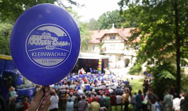 ein blauer Ballon mit der Aufschrift 125 Jahre Kleinwachau, im Hintergrund das Brunnenhaus und eine Bühne mit vielen Menschen davor sitzend