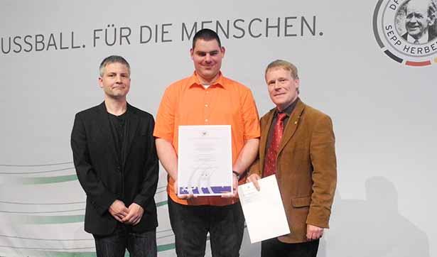 Der Fußballspieler des FC Kleinwachau, Roman Eichler, hält die Urkunde in der Hand. Daneben stehen der Trainer Lutz Höhne und der Vereinspräsident Markus Rebs