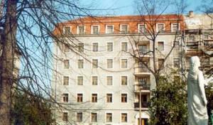 Blick auf ein 6-geschössiges Haus in der Stadt Dresden, rotes Dach, hellgraue Fassade