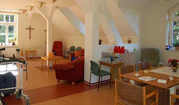 Blick in den Gemeinschaftssal der Seniorenstätte, Dachschrägen an der Seite, ein Holzkreuz am Ende des Raumes