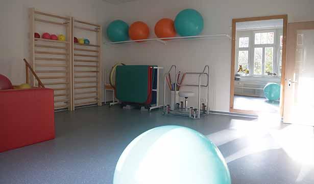 Blick in den hellen Gymnastikraum, ein Spiegel hängt an der Wand, zwei Klettergerüste, Bälle und Turnmatten sind zu sehen