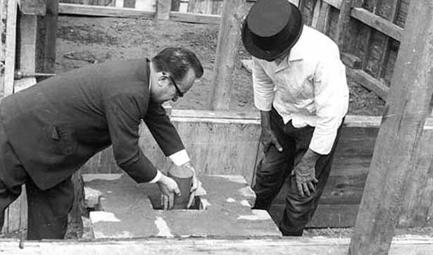 Ein Mann legt eine Schatulle in den Grundstein, ein Bauarbeiter beobachtet das