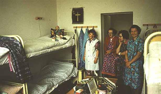 Blick in ein Zimmer, 4 Frauen stehen im Zimmer, 4 Doppelstockbetten stehen im Zimmer