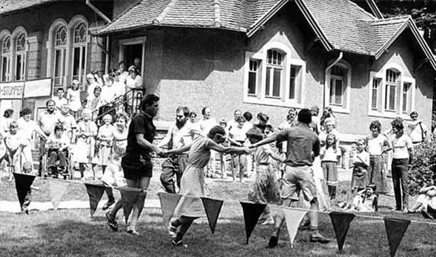 Eine Gruppe tanzt vor der Kirche, viele Zuschauer sehen sich das an