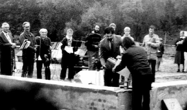zwei Männer legen den Grundstein, dahinter ist eine Bläsergruppe zu sehen