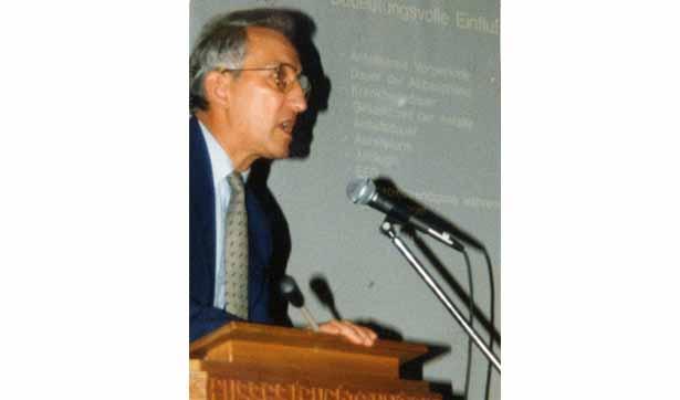 Prof. Todt steht am Rednerpult und hält einen Vortrag, hinter ihm ist ein Beamer-Bild zu sehen