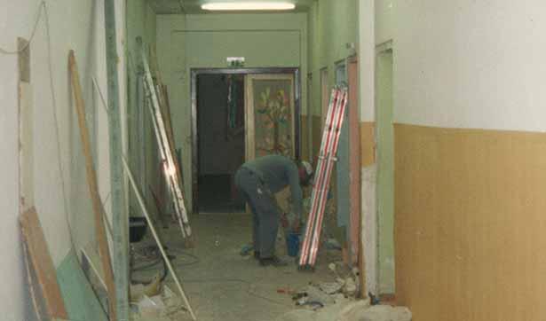 Blick in den Flur, der eine Baustelle ist, ein Handwerker steht vor einer Leiter