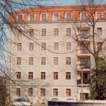 Blick auf das Stadthaus in Dresden, ein Gebäude mit grauer Fassade und rotem Dach
