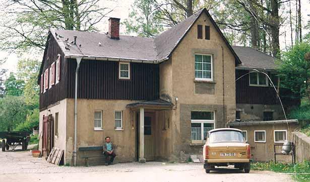 Das Landwirtschaftsgebäude, davor steht ein Trabant, ein Mann sitzt am Eingang