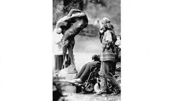 Eine junge Frau und ein Mann im Rollstuhl schauen auf eine Plastik. Die Plastik hat dünne Beine, eine raue Oberfläche, sie deutet einen Menschen an
