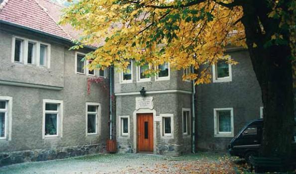 Blick in den Hof der Tobiasmühle, ein altes graues Gebäude, im Innenhof steht ein Baum, dessen Blätter gelb gefärbt sind