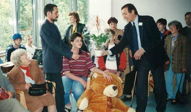 ein Mann übergibt einem Pfleger eine Blume, ein junger Bewohner sitzt dazwischen, er hält einen Plüschtierbären in der Hand, im gesamten Raum sind viele Menschen versammelt