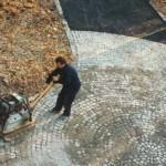 Ein Mann mit einer Rüttelplatte verdichtet das Granitpflaster