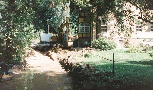 ausgeschateter Unterbau für einen Weg vor dem Brunnenhaus, in dem Graben steht Wasser, im Hintergrund ist ein Bagger zu sehen