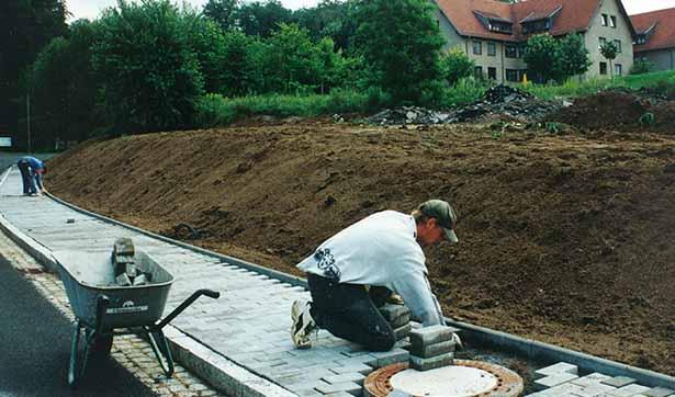 Der Weg zwischen dem Epilepsiezentrum und dem Dorfkern wird gebaut, ein Bauarbeiter verlegt das Betonpflaster, eine Schubkarre steht im Vordergrund