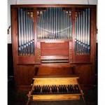 Die neue Orgel, sie besticht durch kirschrotes Holz, davor steht eine Bank