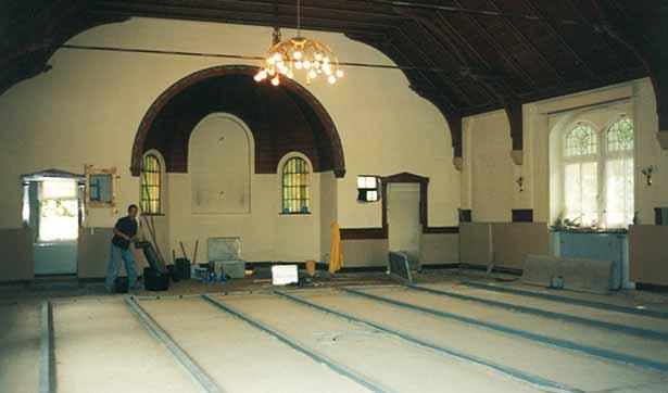 Blick in den Kirchsaal, der Holzfußboden fehlt, man sieht eine Unterkonstruktion und den Estrich