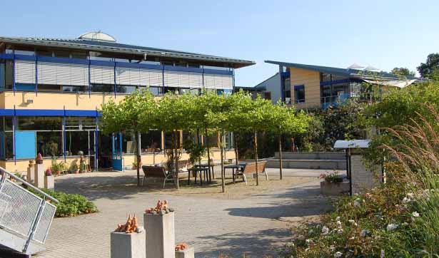 Blick auf den Werkstatthof, große Fensterfront, gelb und blau gestaltete Fassade