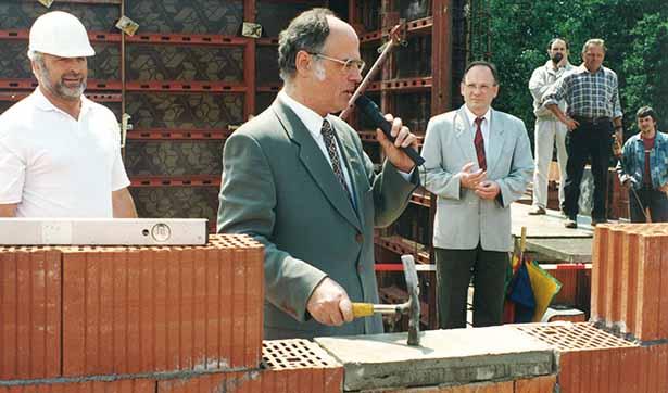 Eine Baustelle: Dr. Hans Geisler schlägt mit einem Hammer auf den Grundstein, hinter ihm steht der Geschäftsführer und der Bauleiter