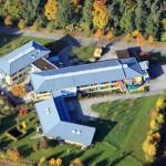 aus der Luft fotografiert: die drei Gebäude der neuen Werkstatt, das bläuliche Dach ist sehr markant
