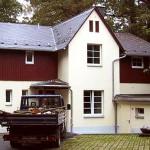 ein saniertes Haus, cremefarbener Anstrich, davor steht ein Transporter