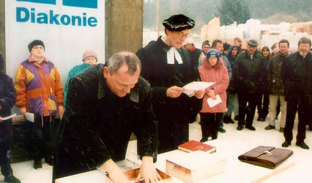 der Schulleiter füllt die Schatulle des Grundsteins, der Pfarrer spricht Segenswünsche, viele Menschen sind versammelt