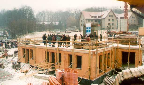 Blick auf die verschneite Baustelle, Menschen sind zur Grundsteinlegung versammelt