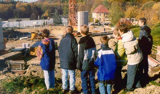 6 Schüler und 1 Lehrerin blicken auf die Baustelle, dort steht schon der Kran