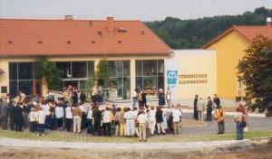 viele Menschen sind vor dem neuen Gebäude versammelt, an der gelben Fassade steh Förderschule Kleinwachau