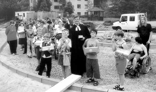 Der Pfarrer und viele Kinder sind zu sehen, jeder hat einen Karton in der Hand, die Wege sind noch gar nicht fertig gestellt