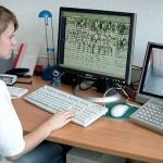 eine Frau blickt auf einen Computer mit EEG-Ableitungen und auf einen Bildschirm, auf dem das Kamerasignal zu sehen ist