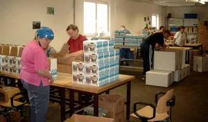 mehrere Beschäftigte verpacken Bierkrüge in Kartons