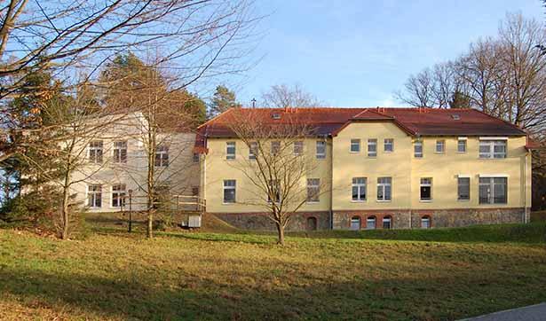 ein zweiteiliges Gebäude, rechts der alte Bau mit einer gelben Fassade, links der neue Anbau mit einer cremefarbenen Fassade