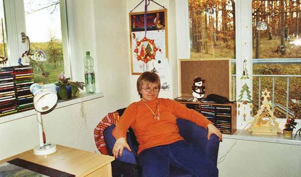 eine Bewohnerin sitzt in ihrem Sessel, sie genießt sichtlich ihr neues Zimmer und den Ausblick auf den Wald