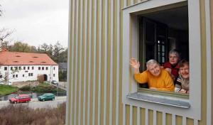 drei Bewohnerinnen blicken aus dem Fenster, hinter dem Gebäude sieht man das Schloß