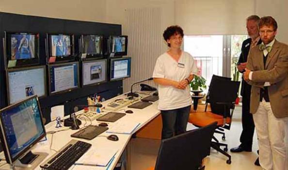 Der Chefarzt erklärt den Monitoringraum, eine Schwester steht an der Seite, an der Wand hängen viele Monitore