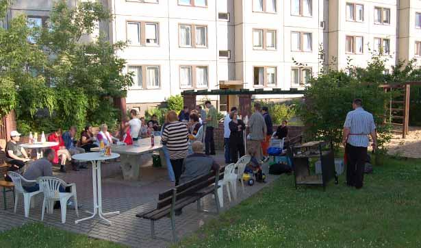 viele Menschen grillen zusammen, sie sitzen und stehen, im Hintergrund sieht man einen Plattenbau