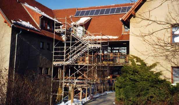 Blick von der Rückseite, es steht ein Gerüst, auf dem Dach wurde eine Photovoltaik-Anlage installiert