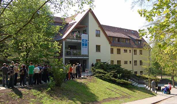 modernisiertes Gebäude, hellgelbe Fassadem am Balkon hängt eine Diakonie-Fahne, vor dem Gebäude stehen sehr viele Menschen