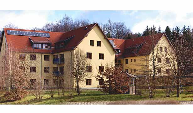 Blick auf das Gebäude von der Rückseite, hellgelbe Fassade, rotes Dach