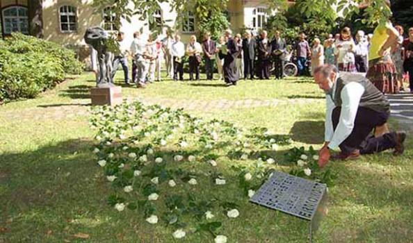Mitarbeiter legen viele weiße Rosen auf den grünen Rasen, sie verbinden das Denkmal und die neue Gedenktafel, im Hintergrund stehen viele Mitarbeiter