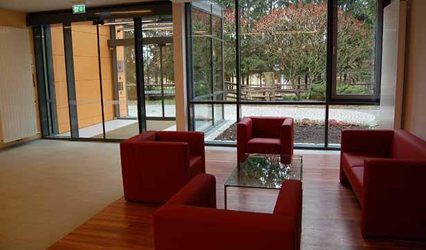 moderner Eingangsbereich: 3 rote Sessel und ein rotes Sofa, Holzfußboden und eine helle Galsfront