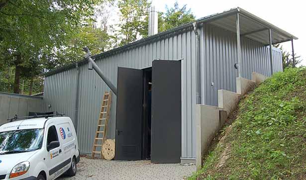 das neue Heizhaus, ein graues gebäude mit einer großen Stahltür