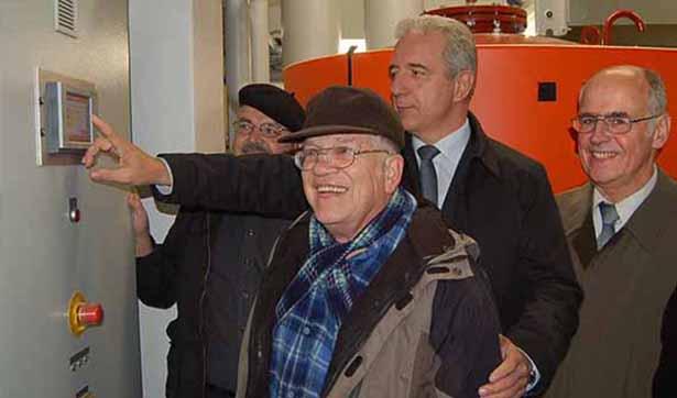 Ministerpräsident Stanislaw Tillich drückt gemeinsam mit einem Bewohner Kleinwachaus den Startknop der neuen Heizungsanlage