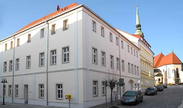 Blick auf einen sanierten Altbau als Eckhaus, cremefarbener Anstrich, im Hintergrund ist die Radeberger Stadtkirche zu sehen