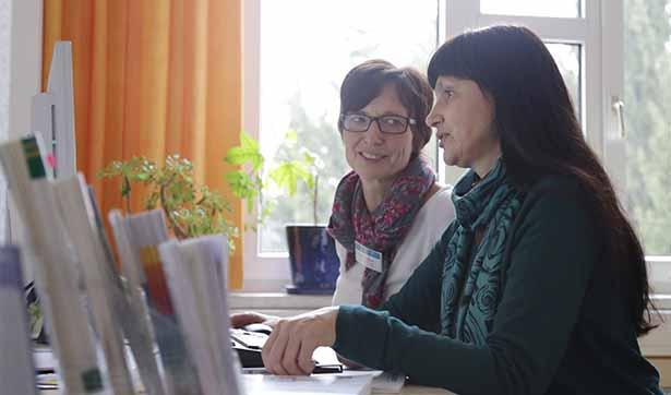 zwei Frauen sitzen am Computer, sie unterhalten sich, im Hintergrund ist ein helles Fenster zu sehen