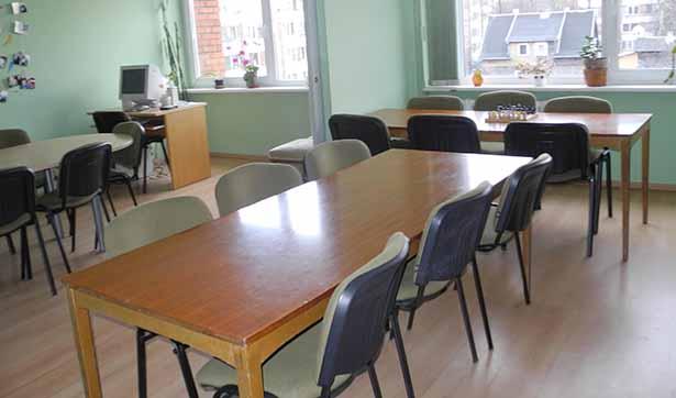 Blick in einen kargen Rau, mit mehreren Tischen und Stühlen und einem Computer