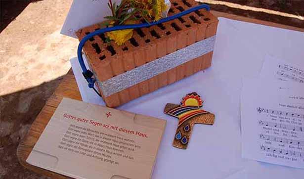 Auf einem Tisch liegen: ein Ziegelstein, eine Tafel mit Segenswünschen und ein buntes Kreuz
