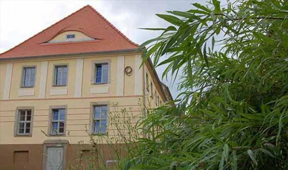 Blick auf die neue Fassade, sie ist gelb mit Akzenten gestrichen, rotes Dach, brauner Sockel