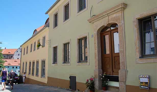 Blick auf die Gebäude in der Gasse, grüne Fassade, historische Fenstereinfassungen, brauner Sockel